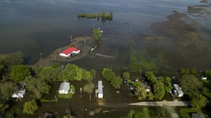 Water from the swelling Mississippi river covers roads and surrounds houses in Foley