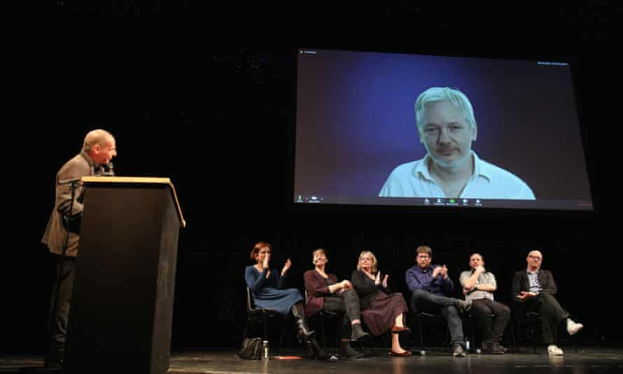 Yanis Varoufakis (left) looks on as Julian Assange speaks via a live broadcast at the official launch of DiEM25.