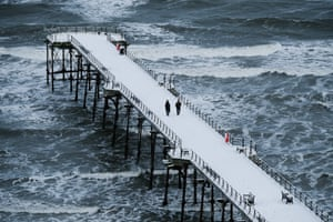 A couple walk along the snow-covered pier in Saltburn-by-the-Sea