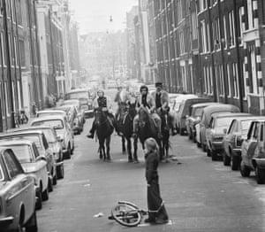 Four men ride on horseback through the streets of Amsterdam