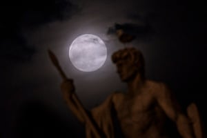 The supermoon shrouded in clouds behind a statue of the Vittoriano in Rome, Italy. April's full moon is considered a supermoon as its near its closest point to Earth.