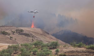 A helicopter carries water to drop on the fire near the village of Gáldar