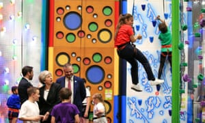 Theresa May watches children use the climbing wall during a visit to the Leisure Box in Brierfield, Lancashire, while on the local election campaign trail.
