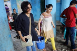 """The artist Leena Kejriwal (left), who came up with the MISSING concept, carries a bucket of paint ready for the next silhouette. Kejriwal's installation work, featuring the same silhouette forms cast in steel, was first displayed at the<a href=""""http://www.theguardian.com/global-development/2014/feb/01/india-art-fair-2014-missing-women""""> India Art Fair last year</a>. Since then it has morphed into a nationwide public art project involving hundreds of participants in cities across India, including Bangalore, Delhi and Chennai."""