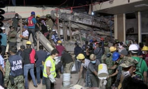 Rescue teams look for people trapped in the rubble at the Enrique Rebsamen elementary school in Mexico City, in this still taken from Mexican TV.