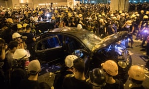 Protesters stand around a damaged car during a confrontation with police in Yuen Long.