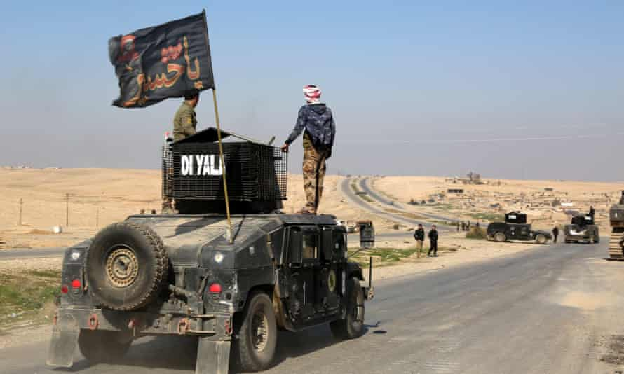 Iraqi army vehicles patrol the airport road, south of Mosul