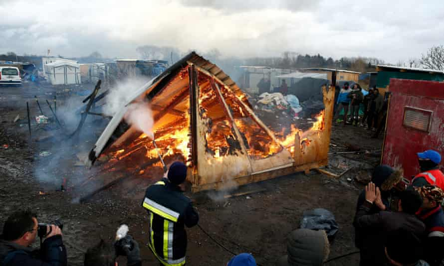 A makeshift shelter in the Calais Jungle is set on fire as part of the camp's demolition.