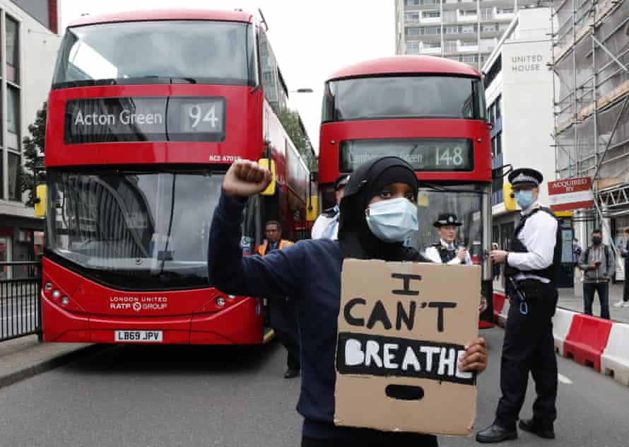 A Black Lives Matter protester blocks a road in Notting Hill, in London.