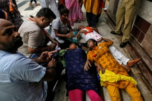People lie on the floor after being affected by teargas in Kolkata, India