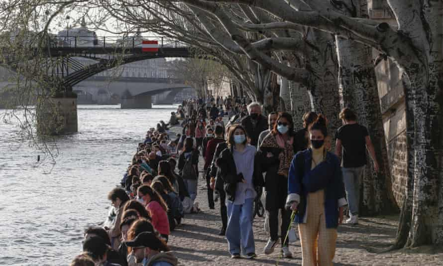 People walk alongside the Seine in Paris on Wednesday