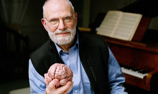 In this 2007 photo provided by the BBC, Neurologist Oliver Sacks poses at a piano while holding a model of a brain at the Chemistry Auditorium, University College London in London.