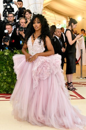 Her frothy pink Versace gown may be light on the religious theme but singer-songwriter SZA topped off the look with a custom halo and bejewelled tear drops.