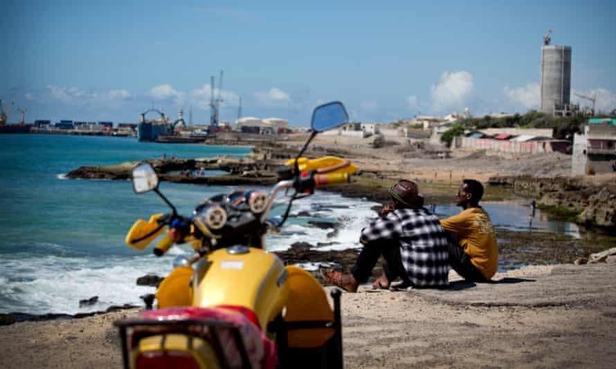 Two men sit looking out over the harbour and port of the Somali capital, Mogadishu.