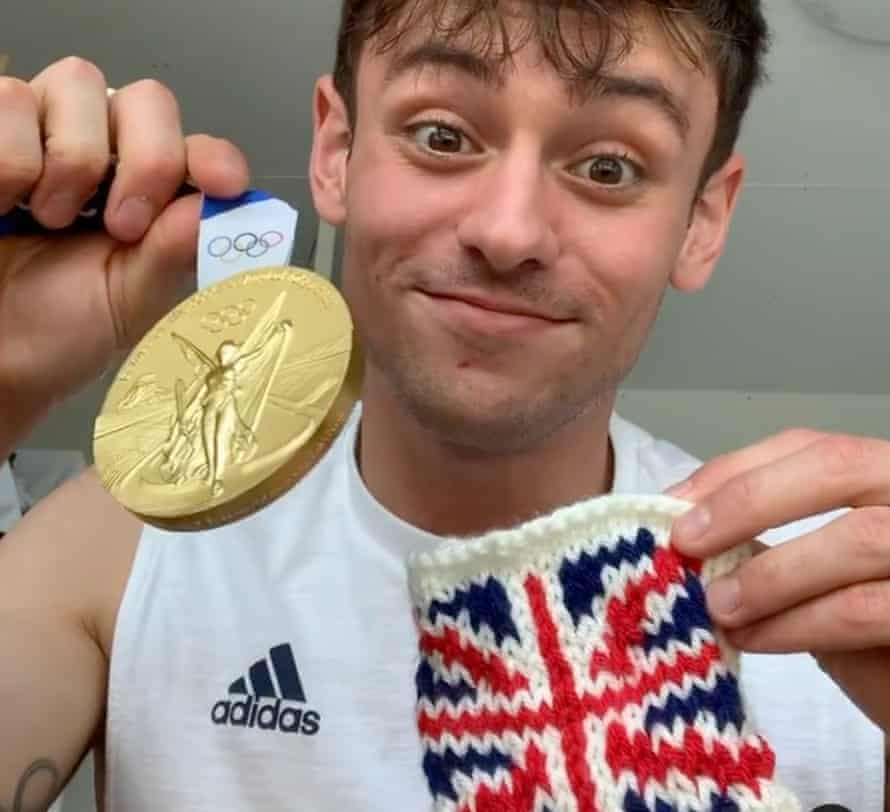 Team GB's Tom Daley holds up his gold medal and the knitted holder.