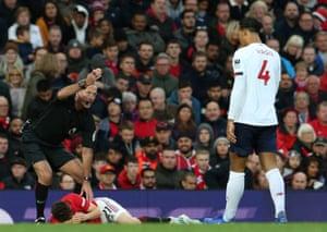 Daniel James of Manchester United lies injured as Virgil van Dijk looks on.