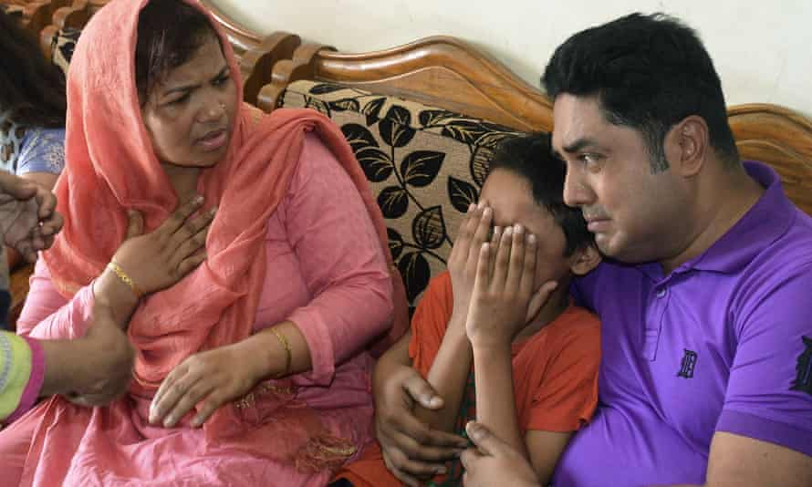 young son of Mahmuda Begum is comforted as he cries