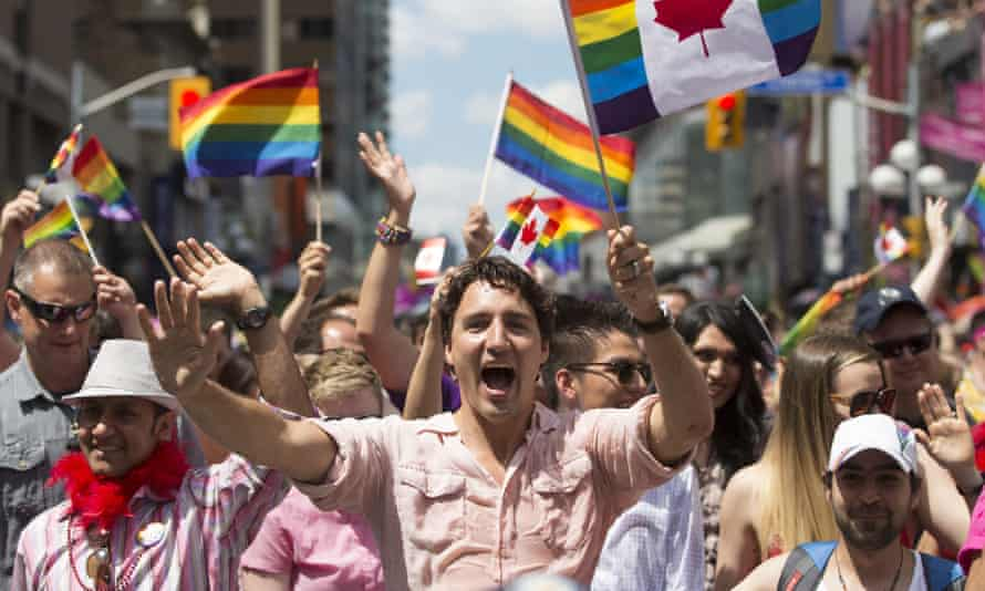Bassel Mcleash (front right, wearing baseball cap) next to Justin Trudeau at the pride parade in Toronto