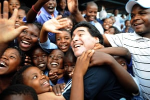 As Argentina's head coach, Maradona is greeted by schoolchildren during his visit to Kgotlelelang school at Winterveldt, South Africa, in January 2010
