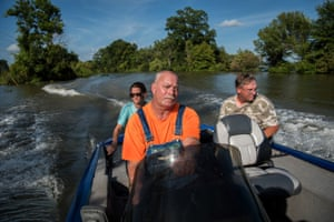 "Carmen Hancock (left to right), James Hancock and Rodney Porter boat down a flooded road near their homes in Valley Park, Mississippi on July 16, 2019. They've spent the past five months helping their elderly neighbors survive in their homes surrounded by floodwater. ""We're living by the good Lord to do what's right,"" said James. ""There's a number of older people living in this neighborhood, and It's just the right thing to do. When the going gets tough, the tough gets going. That's what I live by. You do what has to be done."""
