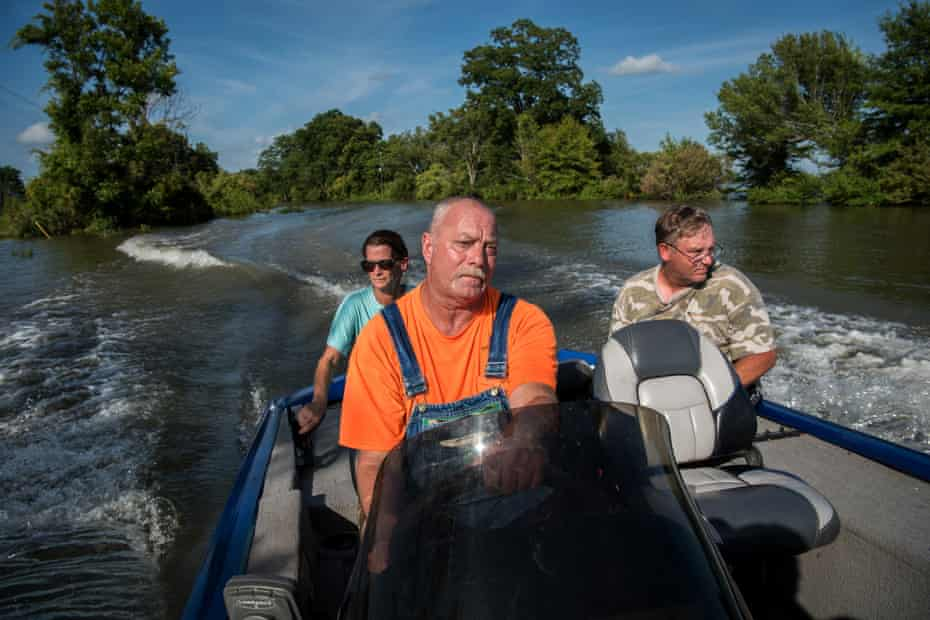 """Carmen Hancock (left to right), James Hancock and Rodney Porter boat down a flooded road near their homes in Valley Park, Mississippi on July 16, 2019. They've spent the past five months helping their elderly neighbors survive in their homes surrounded by floodwater. """"We're living by the good Lord to do what's right,"""" said James. """"There's a number of older people living in this neighborhood, and It's just the right thing to do. When the going gets tough, the tough gets going. That's what I live by. You do what has to be done."""""""