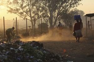 Harare, Zimbabwe: A man sweeps a path near a rubbish dump
