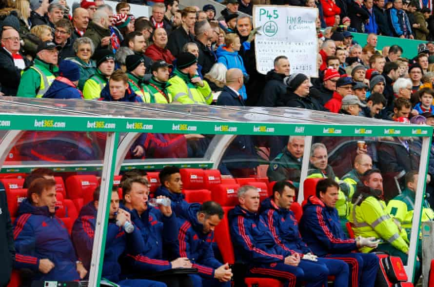 Manchester United manager Louis van Gaal looks on as behind a Stoke fan wearing a José Mourinho mask poses with a P45 banner.