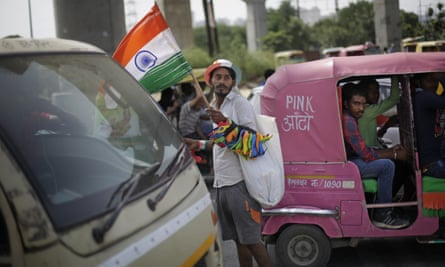 A street hawker sells flags and other merchandise at an intersection in Delhi