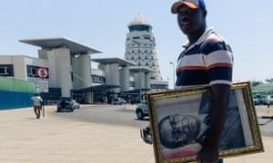 A man carrying a portrait of Mugabe makes his way to Robert Mugabe international airport