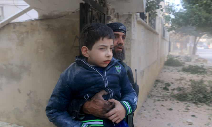 A rescue worker holds an injured boy after what activists said were airstrikes carried out by Russia in Idlib