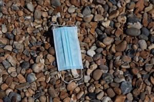 A discarded face mask lies on Brighton Beach