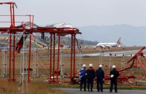 Officials check broken localiser facilities at Hiroshima airport, after an Asiana Airlines Airbus A320 aircraft (seen in background) overran a runway.