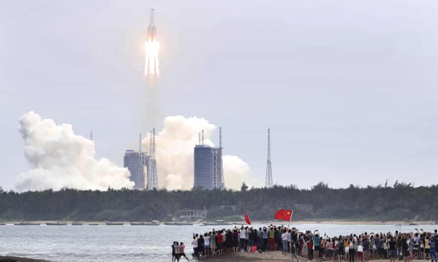 People watch the launch of the Long March 5B rocket from the Wenchang, Hainan province.