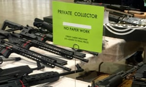 A gun seller at the Great Southern Gun and Knife Show in Atlanta advertises the fact that his customers are not subject to background checks.