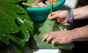 The Colombian chef Eduardo Martínez of the restaurant Mini-Mal wraps fish from the Rio Beni inside of a bijao leaf, to be grilled for a dinner using rainforest products.