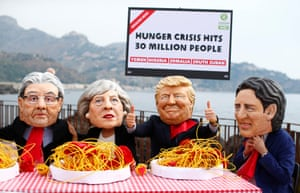 Protestors wear masks depicting the leaders of the G7 countries during a demonstration against world hunger in Giardini Naxos, Sicily, Italy