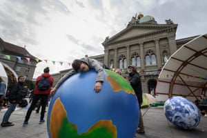 Bern, Switzerland: A climate activist lies on an inflatable globe in front of the Swiss parliament at the start of a week of demonstrations called 'rise up for change'