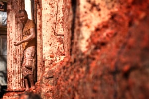A tomato-covered man takes refuge by a column at La Tomatina in Spain