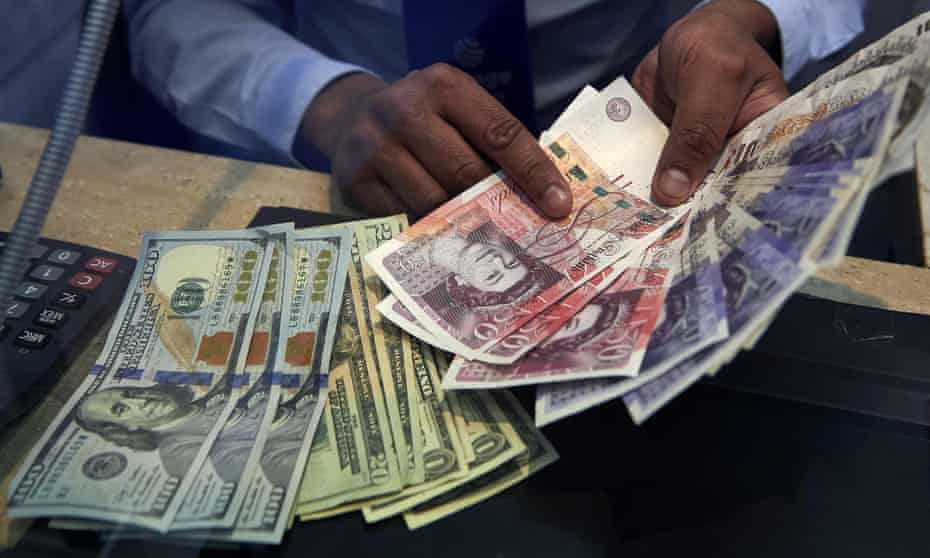 A cashier displays US dollar and British pound Sterling bank notes inside a currency exchange