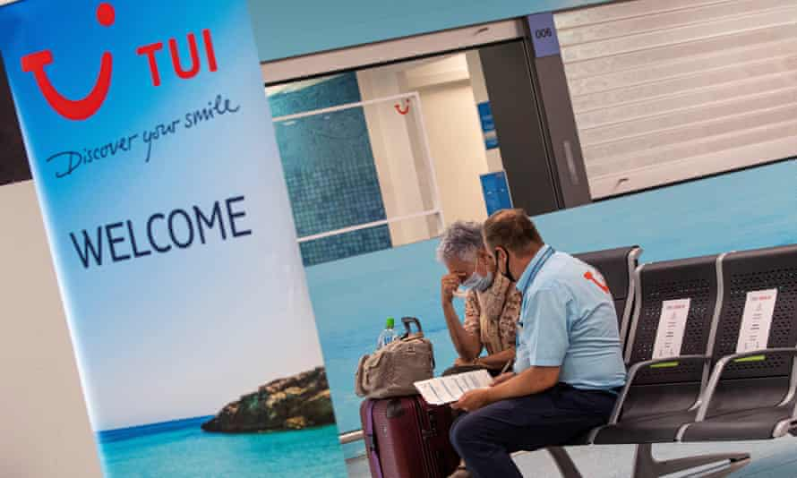 A traveler with her baggage talks with a worker of TUI travel company at Palma de Mallorca's airport.