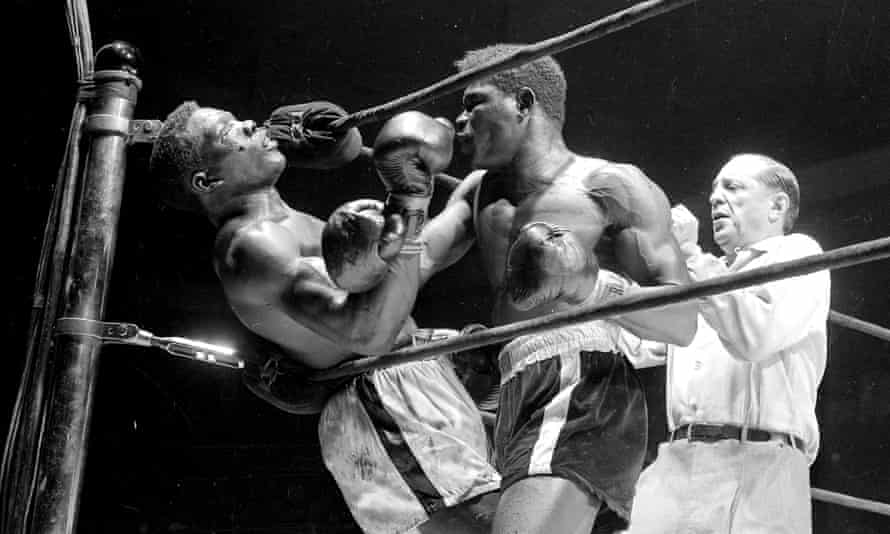 Benny Paret lies helpless against ropes as the flailing fists of Emile Griffith batter him into unconsciousness during 12th round of their welterweight championship fight with referee Ruby Goldstein poised to move in.