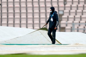 A groundsman pulls on the covers as rain stop play.