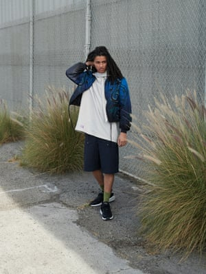 blue and black design printed nylon jacket, pale grey oversized hoodie, black wide legged shorts all from Lanvin, green ankle socks stylists own, black and grey trainers with white sole Adidas