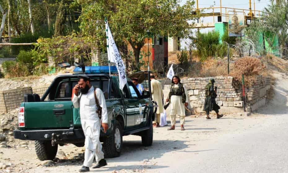 A Taliban member with gun and phone patrols near a pickup truck near the site of a bomb blast in eastern Afghanistan.