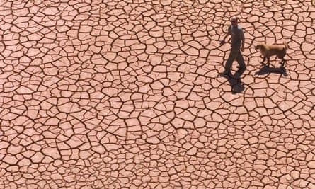 Man and dog walk along the dry, cracked bed of a reservoir.