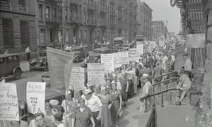 A large crowd marches through New York City in 1937 to demand workers' rights.