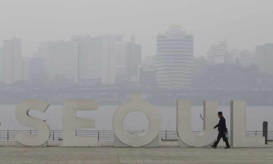 A man wearing a mask to protect from air pollution walks along the Han river at a park in Seoul