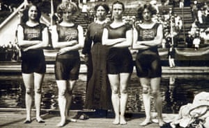 Black and white photo; four young white women with arms folded, wearing dark swimming suits with short legs and the union jack across their chests, stand in front of a pool. An older woman in severe black dress with a white ruff collar stands behind them.