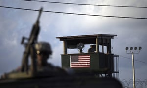 A US trooper mans a machine gun as a guard looks out from a tower in front of the detention facility at Guantanamo Bay.