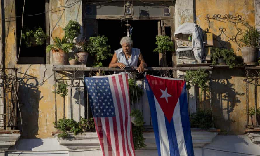Javier Yanez stands on his balcony decorated with US and Cuban flags in Old Havana.